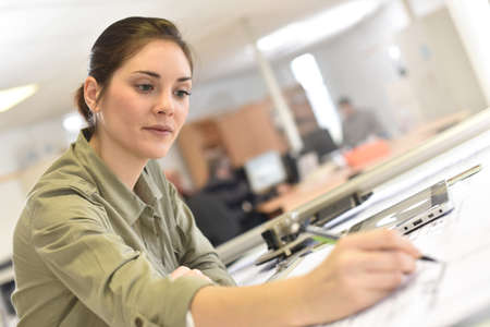 graphic designing: Woman architect working on drawing table in office Stock Photo
