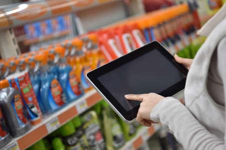 merchandiser: Closeup of digital tablet held by merchandiser in supermarket aisle