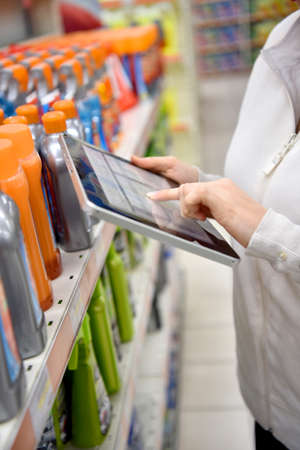 registering: Woman merchandiser checking products available with digital tablet Stock Photo