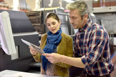 Man in printing house showing client printed documents Standard-Bild
