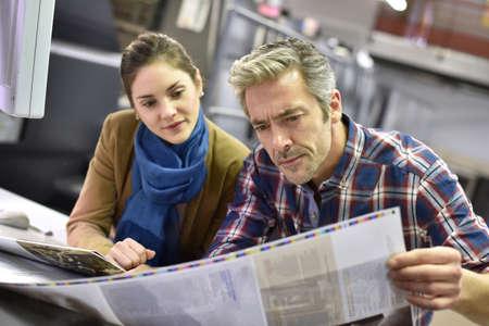 impresión: Hombre en casa de impresión que muestra los documentos del cliente impresa