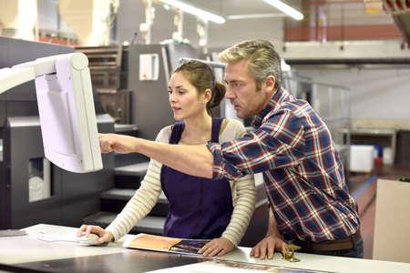Man werken met een leerling in drukkerij Stockfoto - 50961618