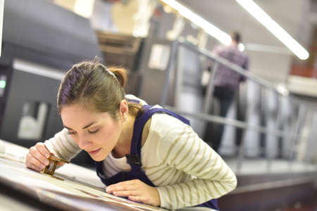 Woman in printing house using magnifying glass Foto de archivo