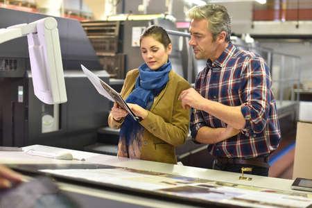 Hombre en casa de impresión que muestra los documentos del cliente impresa