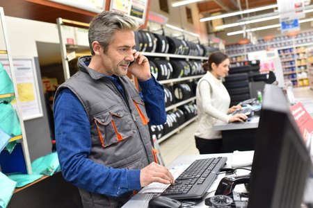 Mécanicien dans la voiture atelier de réparation de parler au téléphone