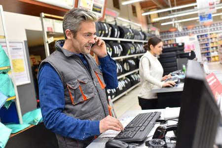 vendedor: Mecánico en el taller de reparación de automóviles, hablando por teléfono Foto de archivo