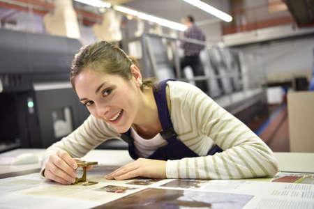 Vrouw die in drukkerij, het controleren van document