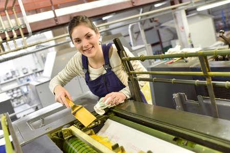Woman in printshop preparing machine Standard-Bild