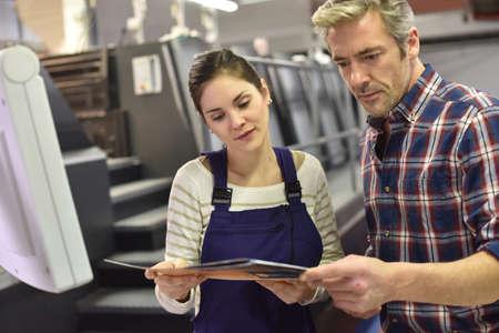impresión: Hombre que trabaja con el aprendiz de imprenta
