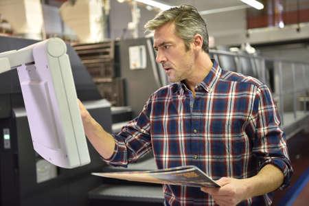 Hombre que trabaja en la máquina de impresión en la fábrica de impresión