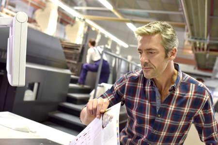 Mens die aan drukmachine in print fabriek