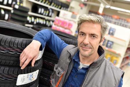 hombres maduros: Mecánico teniendo neumático nuevo para el taller
