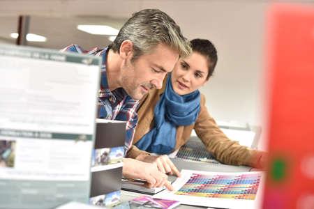 Cliente en imprenta el control de trabajos antes de la impresión final Foto de archivo