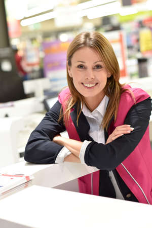 assistant: Customer service woman standing at the reception desk of supermarket