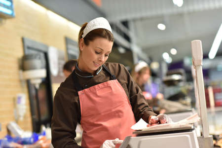 Vrouw varkensvlees slager serveren worstjes aan de klant