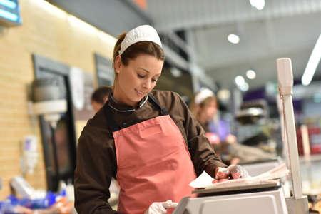 Woman pork butcher serving sausages to customer
