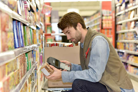 merchandiser: Sales assistant scanning products before putting for sale Stock Photo