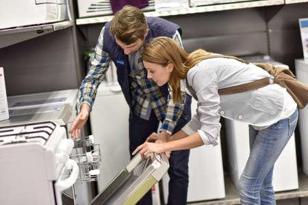 Vendedor ayudar al cliente con la elección de lavavajillas