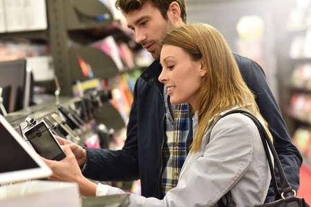 choosing: Couple in store choosing smartphone