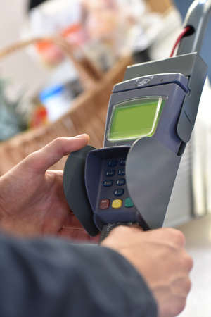 introducing: Closeup of customer hand introducing credit car into bank terminal