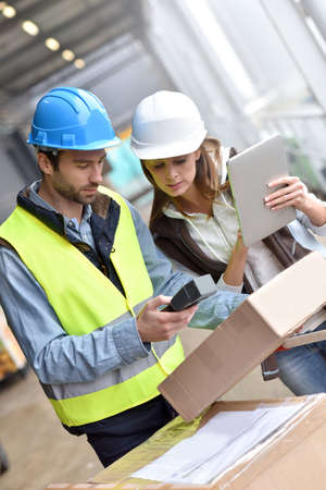 Store manager with warehouseman checking goods reception Stock Photo
