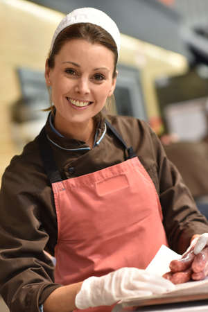 supermarkets: Woman pork butcher serving sausages to customer Stock Photo
