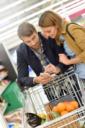 shopping list: Couple in supermarket reading shopping list on smartphone Stock Photo