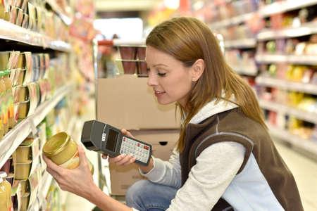 Sales assistant scanning producten alvorens ze op de planken