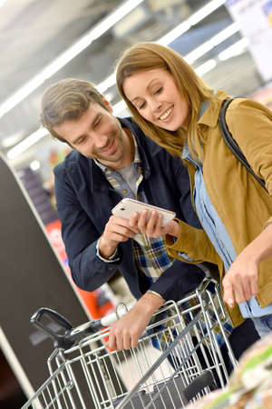 35 years old man: Couple in supermarket reading shopping list on smartphone Stock Photo