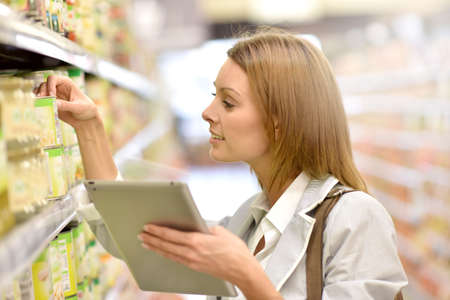 hypermarket: Woman in supermarket checking shopping list on tablet
