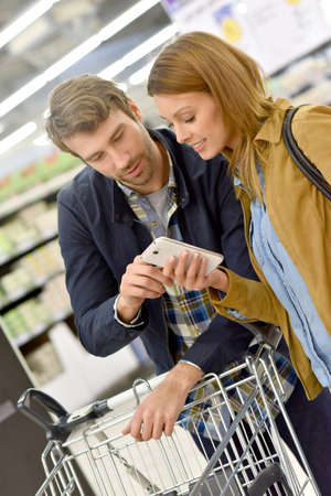 35 to 40 years old: Couple in supermarket reading shopping list on smartphone Stock Photo