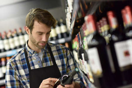 oenology: Wine specialist putting bottle up in winery section of supermarket