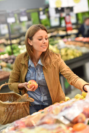 35 to 40 years old: Woman at the grocery store buying fruits and vegetables