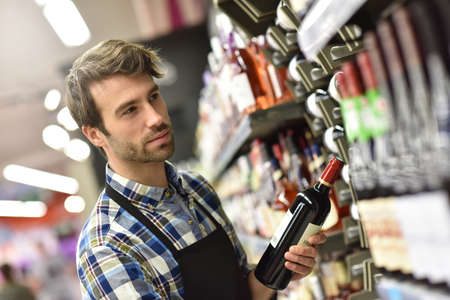 merchandiser: Wine specialist putting bottle up in winery section of supermarket