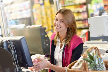 Portret van glimlachende kassier werken in supermarkt
