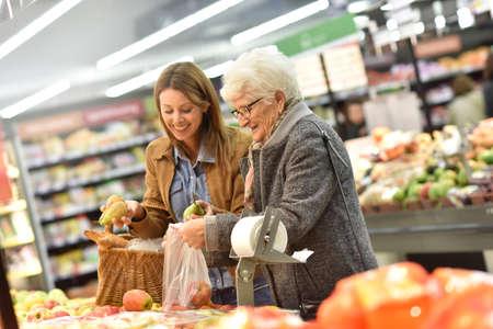 jubilados: mujer de edad avanzada con una mujer joven en el supermercado