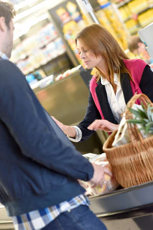paying: Portrait of cashier with customer paying grocery products Stock Photo