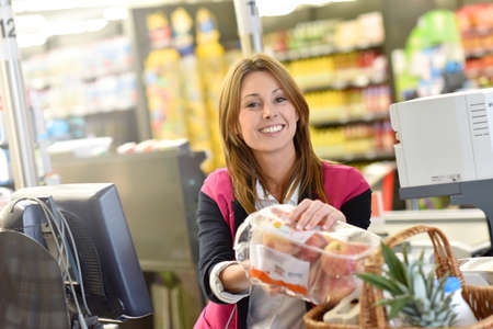 grocery store checkout: Portrait of smiling cashier working in grocery store Stock Photo
