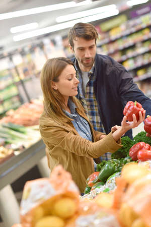 35 years old man: Couple at the grocery store buying fruits and vegetables