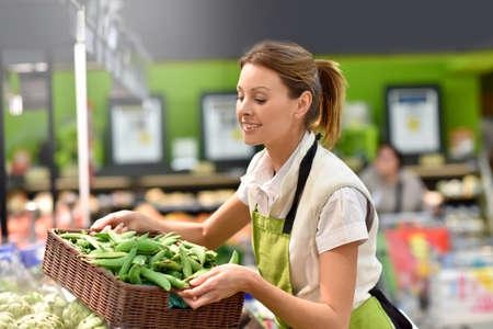 empleado de supermercado poner las verduras en las estanterías Foto de archivo