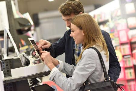 choosing: Couple in store choosing digital tablet