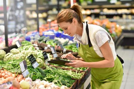 merchandiser: Supermarket employee putting vegetables in shelves