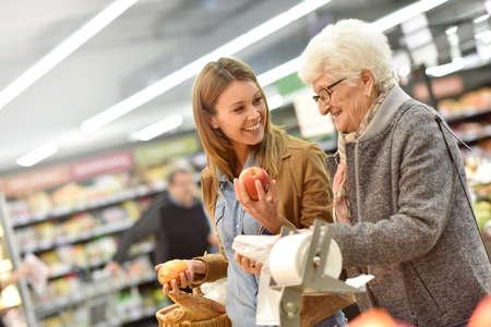 helping: mujer de edad avanzada con una mujer joven en el supermercado