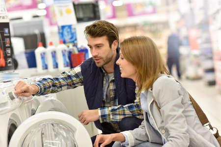 Verkoper helpen klanten bij het kiezen van een wasmachine Stockfoto - 51881791