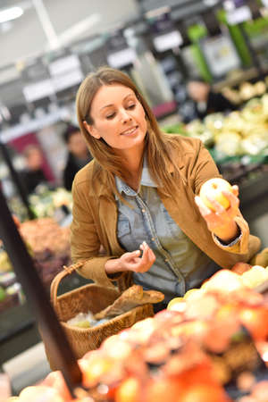 retail store: Woman at the grocery store buying fruits and vegetables