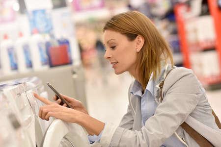knelt: Woman in supermarket comparing washing machine details with smartphone