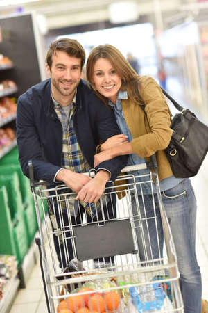 35 to 40 years old: Couple pushing shopping cart in supermarket Stock Photo