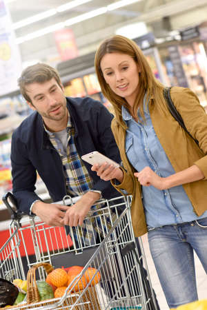 35 to 40 years old: Couple in supermarket doing grocery shopping with help of smartphone