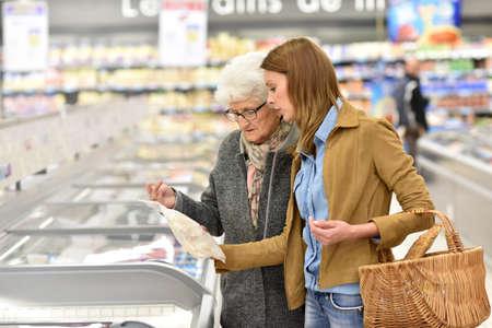 Bejaarde vrouw met een jonge vrouw in de supermarkt Stockfoto - 51881750