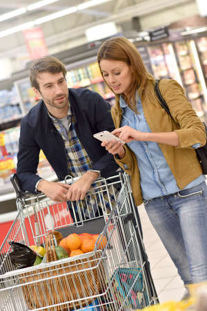 35 years old man: Couple in supermarket doing grocery shopping with help of smartphone